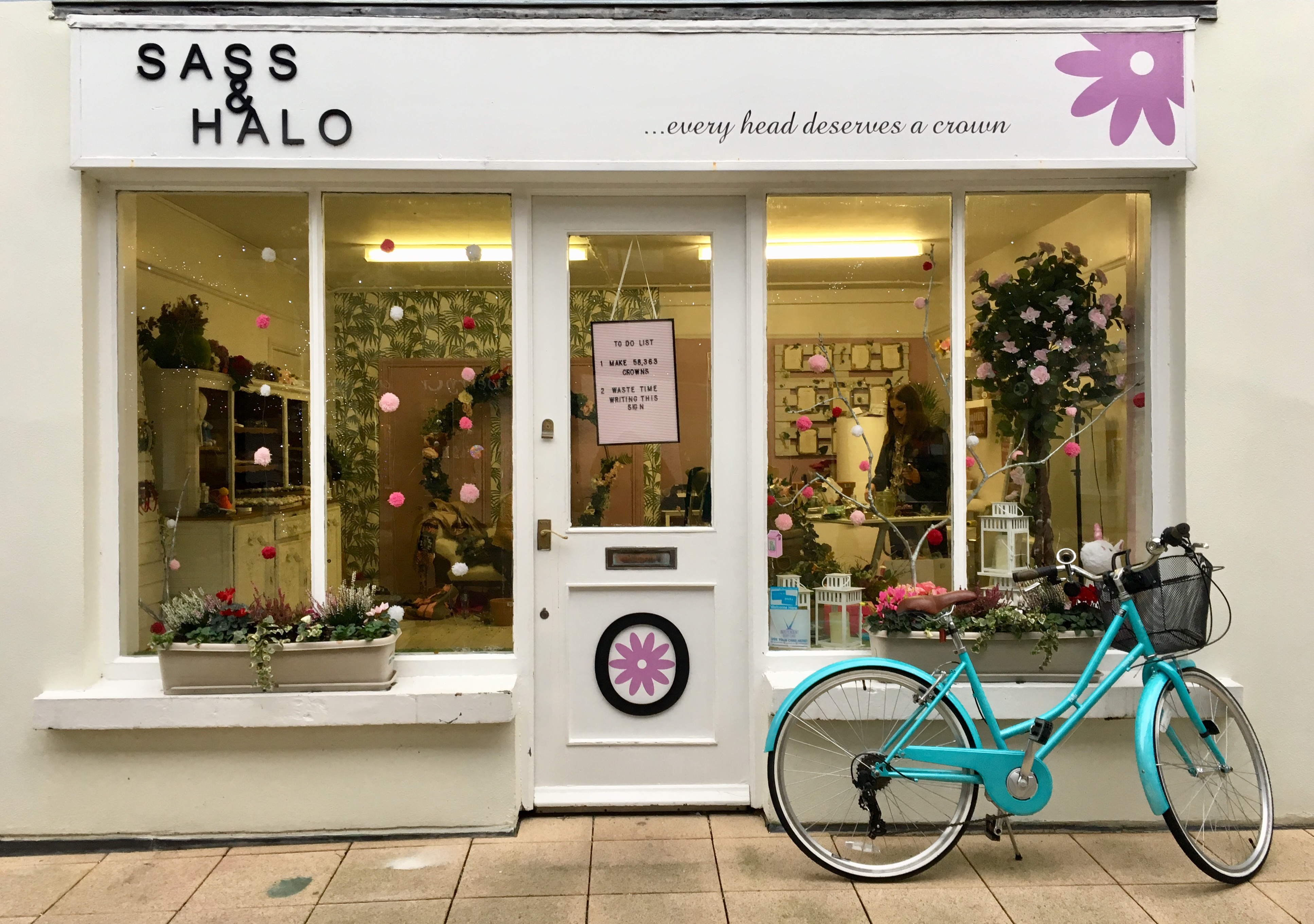 White shop front with flower crowns and blue bicycle parked outside
